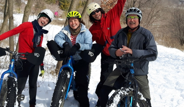 People posing with fat bikes on snowy trail.