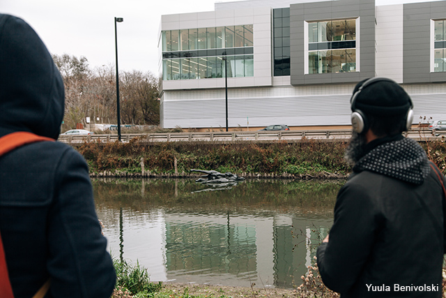 Two men watch the performance next to the Don River.